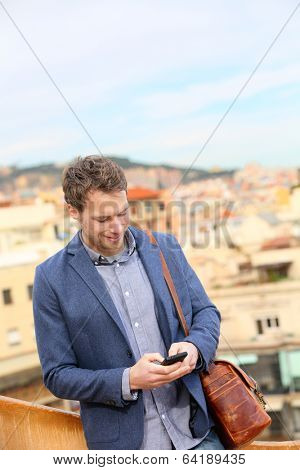 Young urban businessman professional using smartphone using app texting sms message on smart phone wearing trendy suit jacket in Barcelona, Catalonia, Spain. Caucasian male fashion model.