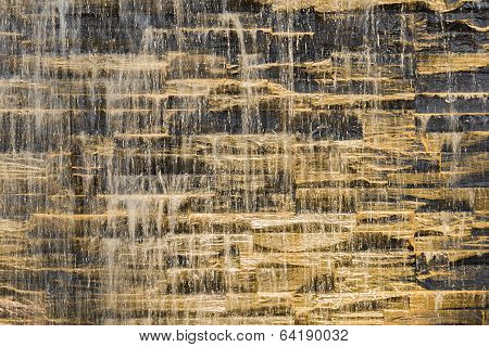Falling Water Stream Against Stonework Rough Texture