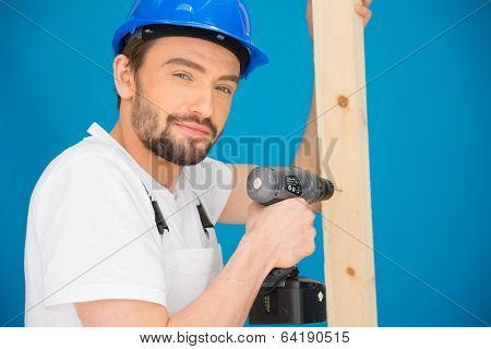 Builder using a drill on a plank of timber turning and looking at the camera with a quizzical serious expression