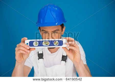 Workman viewing a spirit level concentrating as he bends forwards trying to read the position of the bubble to ensure a horizontal line