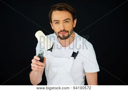 Attractive bearded young painter in dungaress standing looking at the camera holding up a white paint roller on a dark background