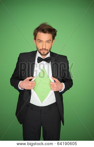 Man in a suit and bow tie opening his white shirt revealing his chest with a blank green t-shirt in a concept of eco activism , on a green background