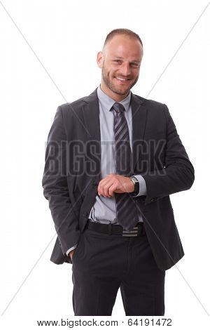 Happy businessman raising arm to check time on wristwatch, smiling, happy.