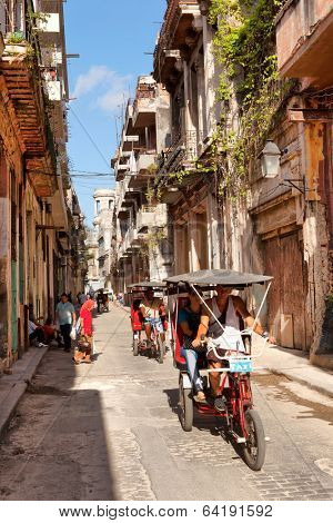 HAVANA - MAY 15: The urban cityscape, pedicab on the road on May 15, 2013 in Havana, Cuba