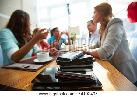 Heap of modern gadgets with group of friends on background