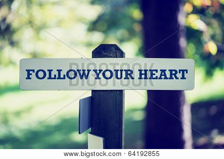 Old Rustic Signpost With Follow Your Heart Sign
