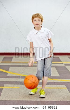 Boy playing with basketball in a schoolyard of an elementary school