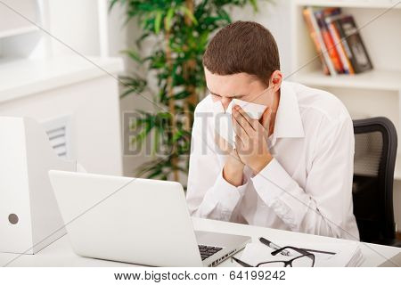 man sneezing while working in office