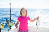 pic of troll  - Blond kid girl fishing tuna little tunny happy with trolling catch on boat deck - JPG