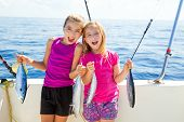 foto of fisherwomen  - Happy tuna fisherwomen kid girls on boat with fishes trolling catch - JPG