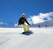 pic of snowboarding  - Young girl snowboarder in motion on snowboard in mountains - JPG