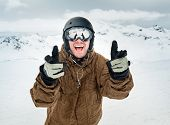 stock photo of snowboarding  - Cheerful snowboarder in protective helmet and mask showing sign happy on the background beautiful mountains - JPG