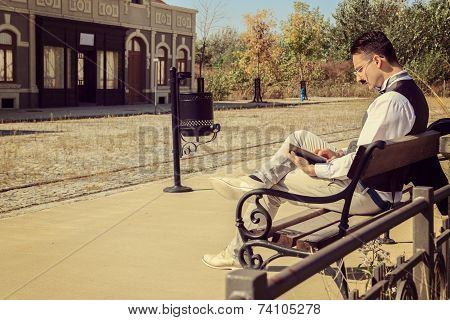 Man In Suit With Glasses And Whiskers Reading Book In The Old Town While Sitting On Bench In Park