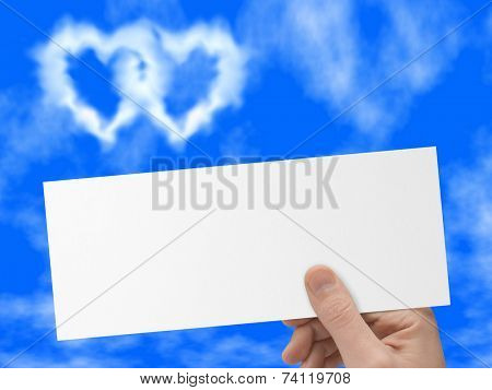 Postcard in hand, blue sky and heart-shaped clouds ( love, valentine's day )