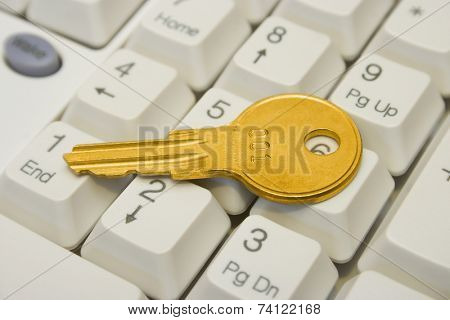 Golden key on computer keyboard, close-up