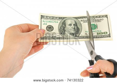 Hands with scissors cutting money isolated on white background