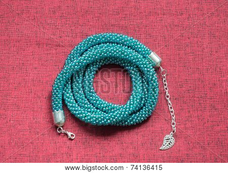 Necklace Of Color Aquamarine On A Textile Background