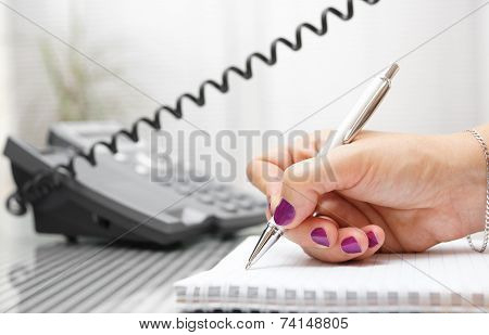 Businesswoman Is Talking On The Phone And Taking Notes