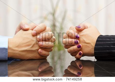 Man And Woman Siting At A Desk With Hands Clasped. Marital Problems, Conflicts And Stubborn Concept