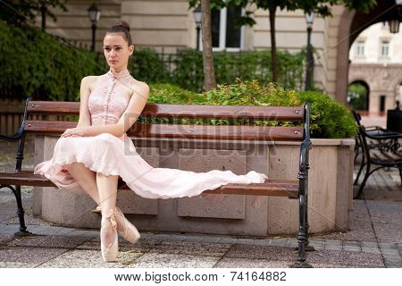 Young beautiful ballerina relaxing on bench