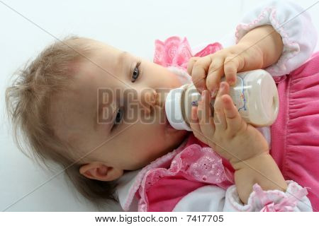 Pretty Baby Girl Is Drinking Milk In A Bottle