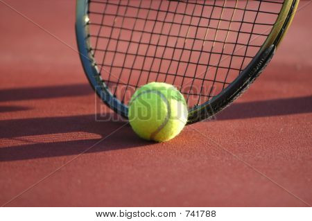 tennis ball resting against racquet