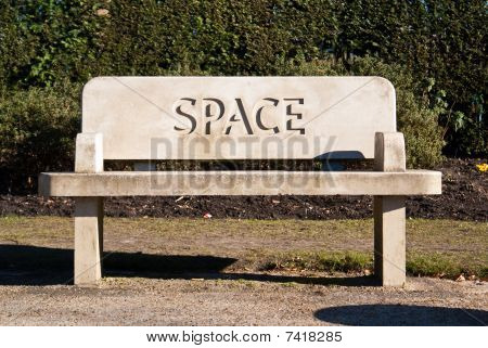 A Stone Bench In A Park With The Word
