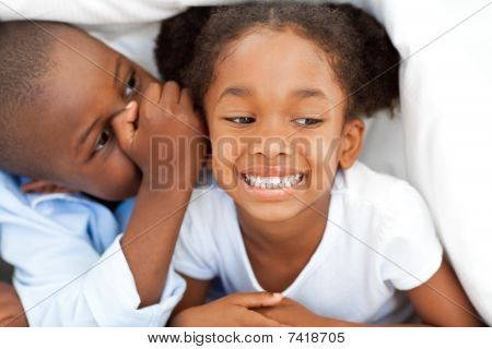 Ethnic Little Boy Whispering Something To His Sister