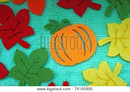 Pumpkin And Colorful Maple Leaves Out Of Felt On A Light Green Fabric As A Background