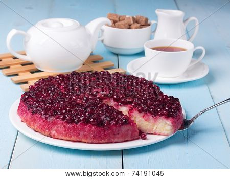 Cranberry Pudding On Blue Wooden Table With Cup Of Tea