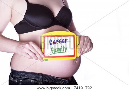 pregnant woman clothed in black bra and jeans holding a toy slate with crossed