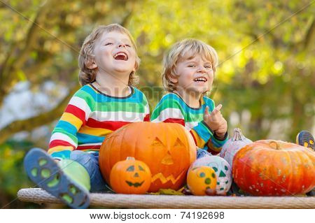 Two Little Sibling Boys Making Jack-o-lantern For Halloween In Autumn Garden