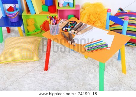 Interior of classroom at school. Crayons and paper on table