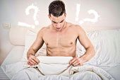 stock photo of masturbate  - surprised half naked young man in bed looking down at his underwear at his penis under white covers sheet in badroom - JPG