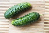 stock photo of cucumber slice  - Two fresh pimply cucumbers on a chopping board - JPG