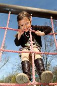 stock photo of young girls  - Young girl enjoys climbing up a rope ladder in a children - JPG