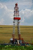 stock photo of  rig  - Color shot of a shale gas drilling rig on a field - JPG