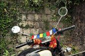 picture of himachal  - Tibetan Buddhist prayer flags are supposed to protect a motorbike in Dharamsala - JPG
