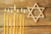 stock photo of hanukkah  - Hanukkah candle on wooden background - JPG