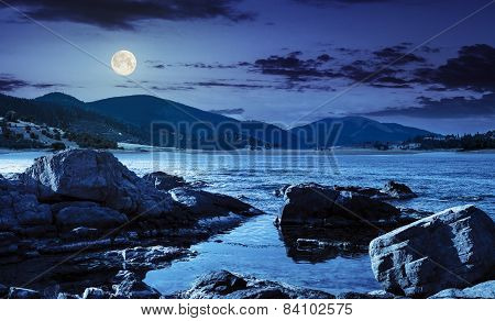 Lake With Boulders In Mountains At Night