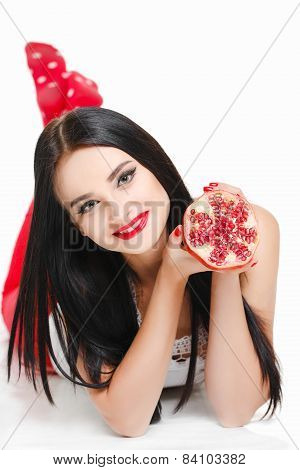 Portrait of a beautiful young woman with a pomegranate.