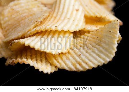 Ridged fried potato crisps on black