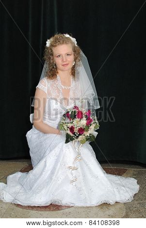 Young blonde bride posing for the camera holding flower bouquet