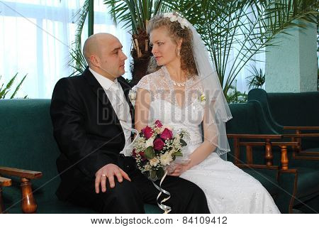 Young bride and groom posing for the camera indoors