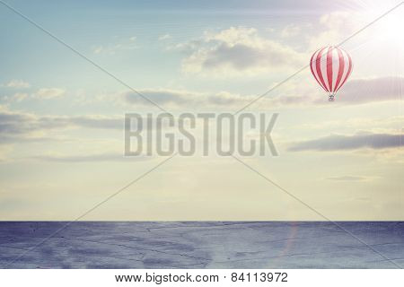 Concrete floor on background of clouds, sun with air balloon