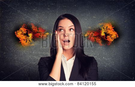 Surprised woman with fire from ears. Concrete gray wall as backdrop