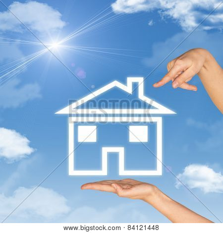 House icon on hand. Second hand points to house. Background of sky, clouds and sun