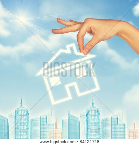 Hand holding house icon. Background of sky, clouds and sun