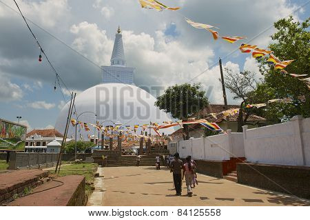People go to the Ruwanwelisaya stupa in Anuradhapura, Sri Lanka.