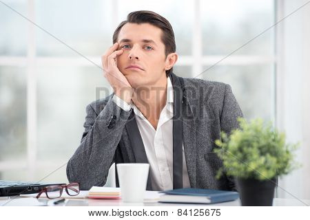 Businessman is bored while working in office